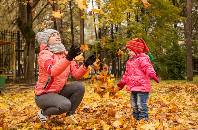Madre y niña jugando con hojas secas